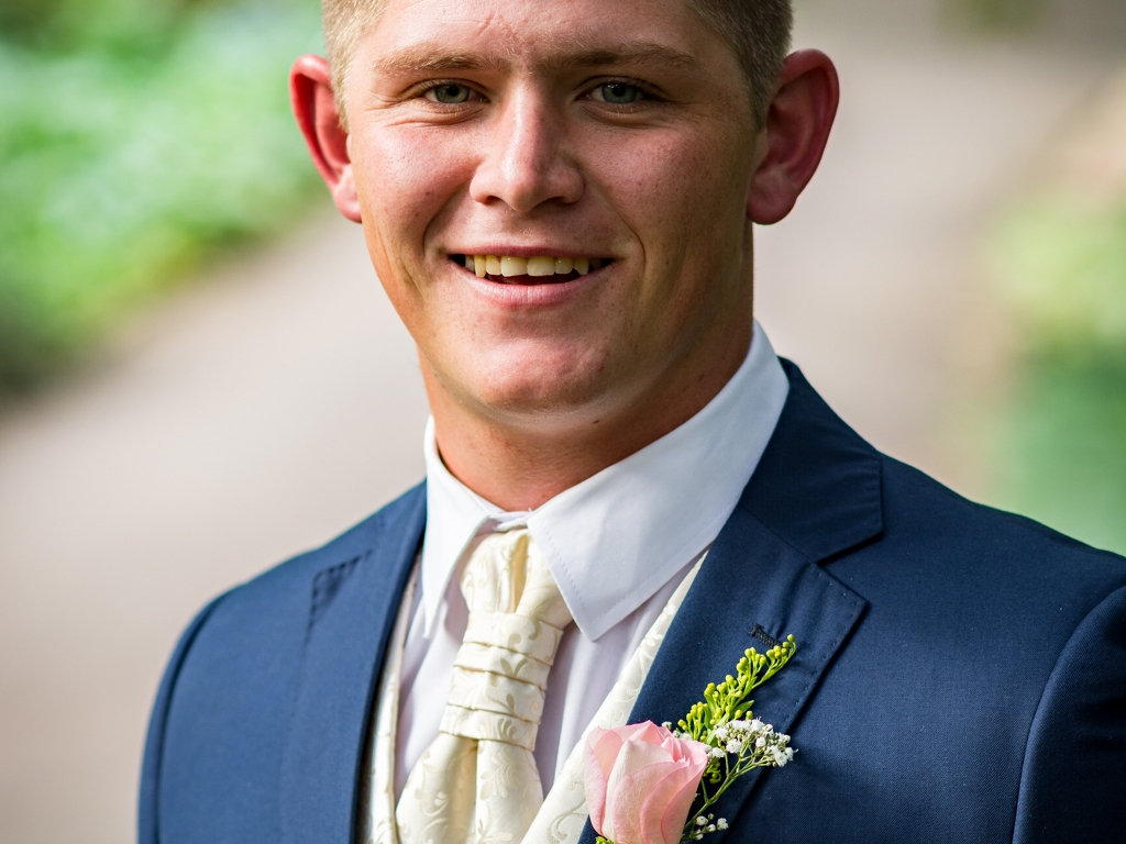 groom with a tie and flowers