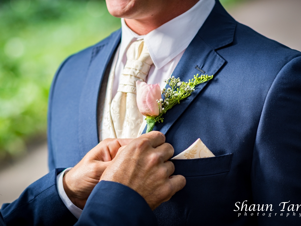 groom getting his tie fixed in a suit