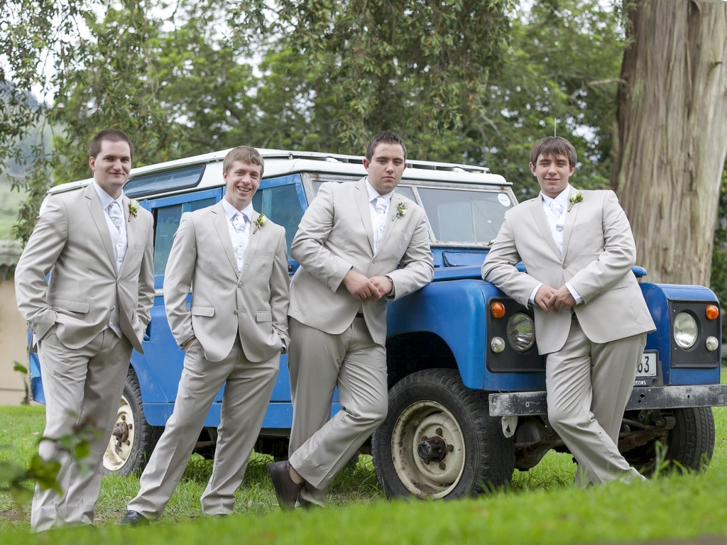 groom and groomsmen posing around a car