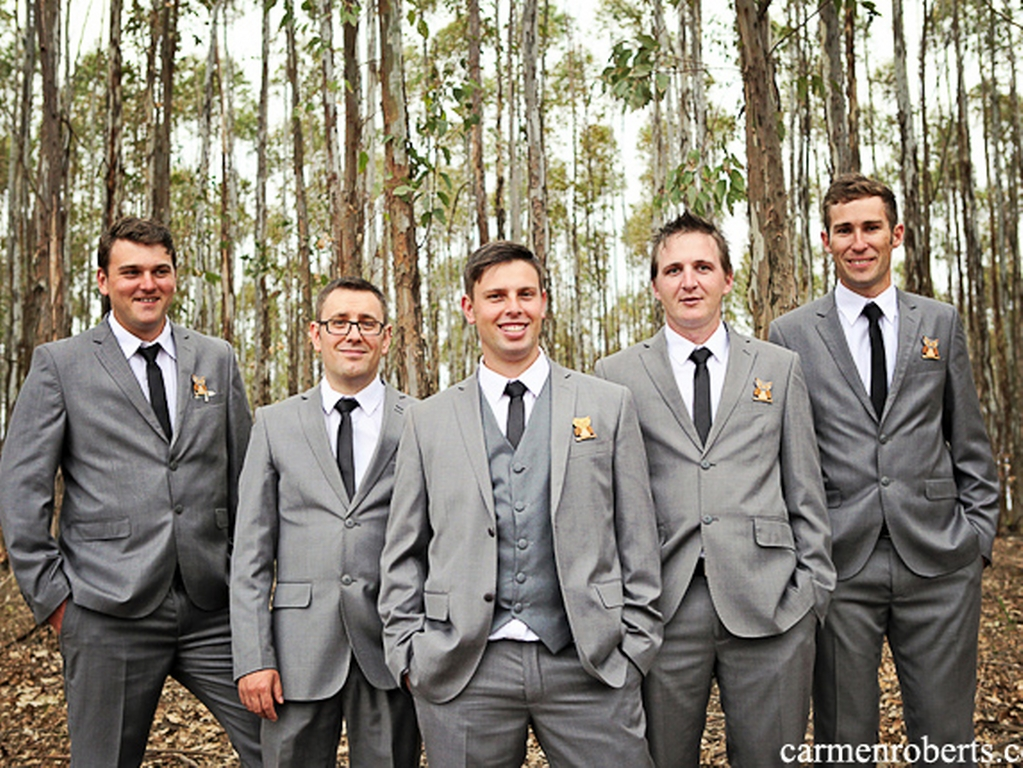 groom and groomsmen standing in a forest in suits