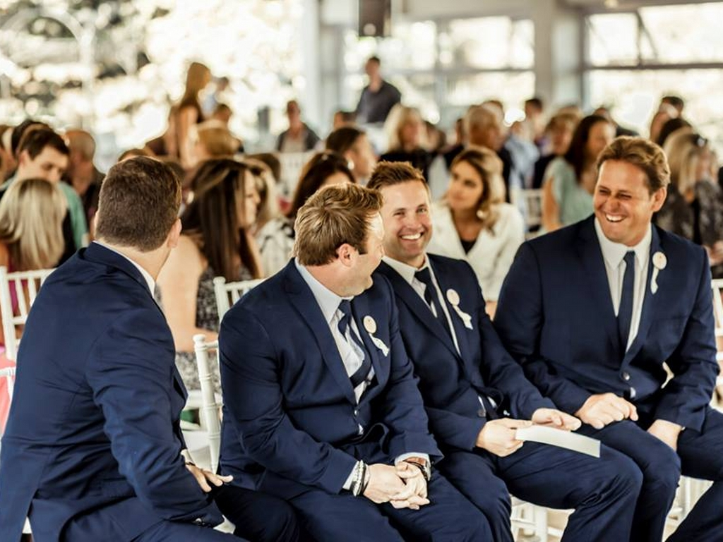 groomsmen sitting at wedding having a laugh
