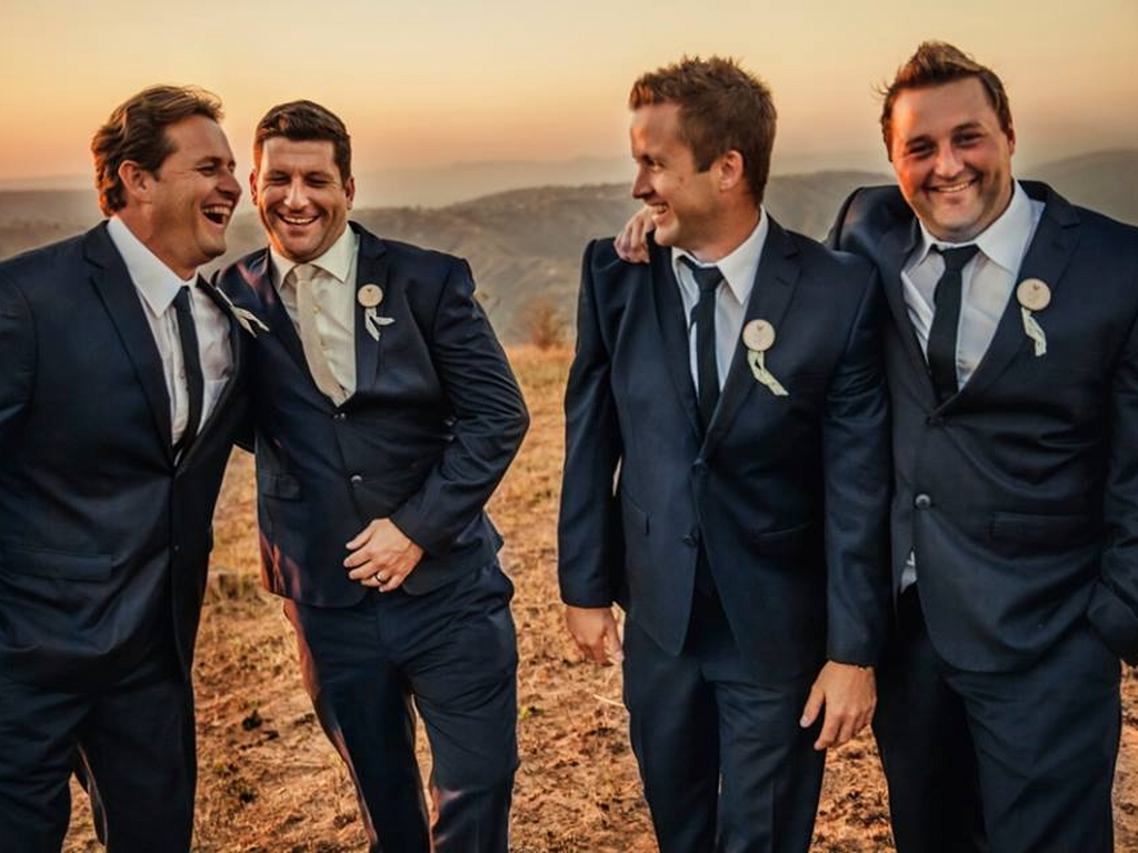 groomsmen and groom laughing in a field
