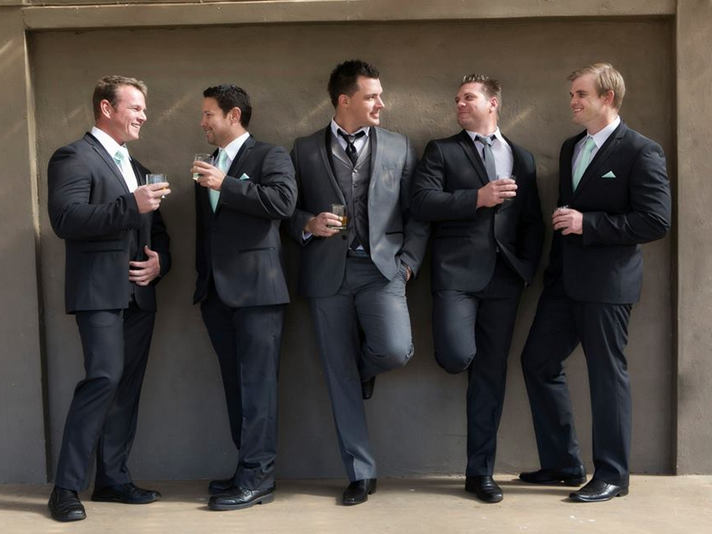 groom and groomsmen posing against a wall in suits