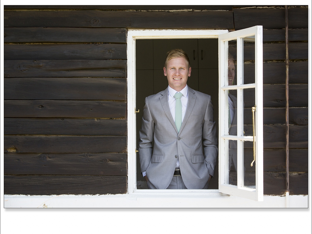 groom looking through a window in a suit