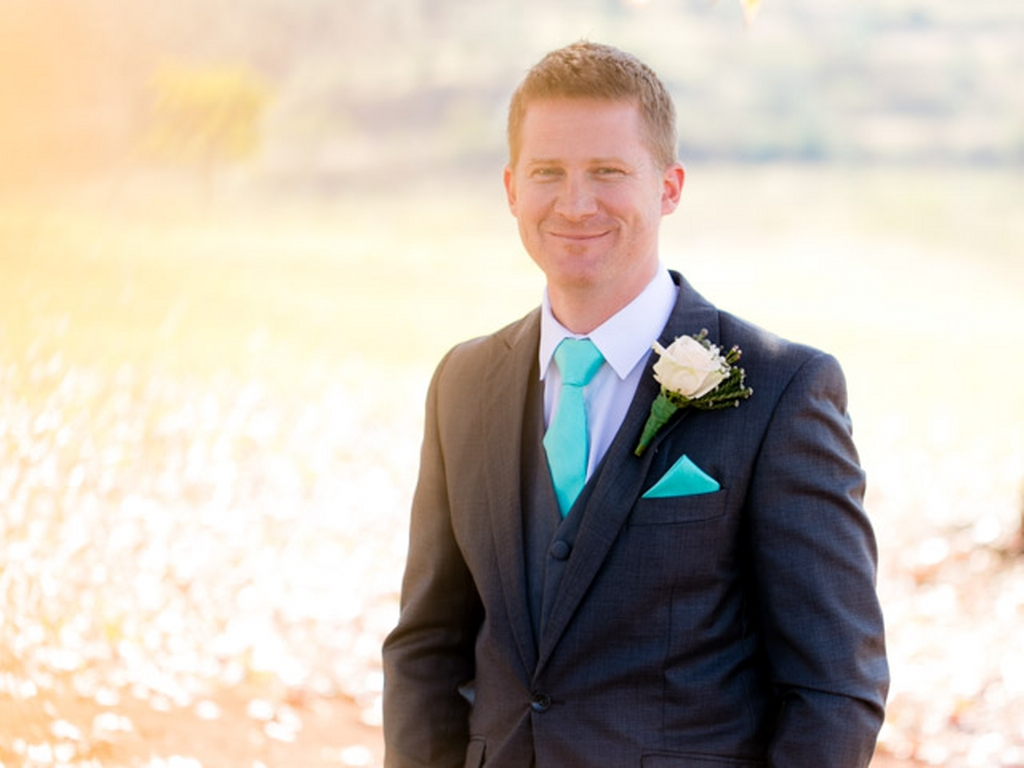 groom with a tie and flower wearing a suit